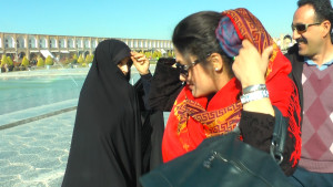 A member from the Islamic Revolutionary Guard Corps warns a woman about her lax headscarf appearance.