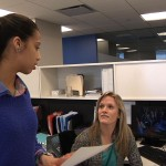 Delilah Nieves assists a colleague at her internship with ExecComm.